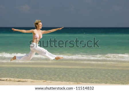 young blond woman jumping on the beach - stock photo