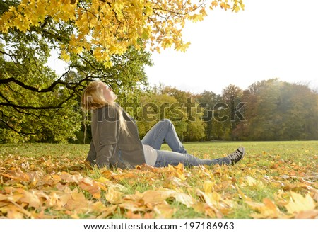 young blond woman lying in autumn park - stock photo