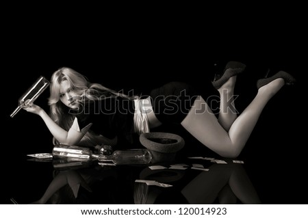 Young blond woman lying on floor holding empty bottle of wine and playing cards, monochrome image - stock photo
