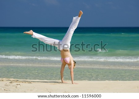 young blond woman making cartwheel on the beach - stock photo