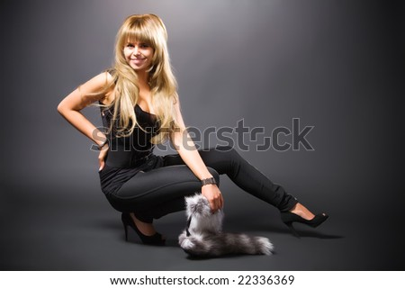Young blond woman on dark background. - stock photo
