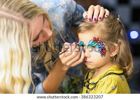Young blond woman painting the face of a little girl - stock photo