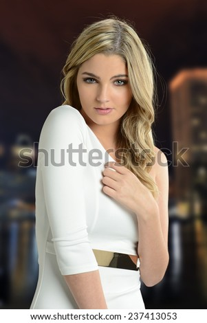 Young Blond Woman portrait at night with city skyline on the background - stock photo