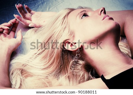 young blond woman portrait lying,  indoor shot - stock photo