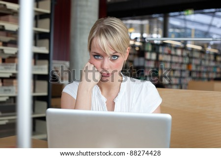 young blond woman pouts in front of her laptop/young blond woman pouts - stock photo