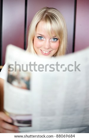young blond woman reads a newspaper/woman with a newspaper - stock photo