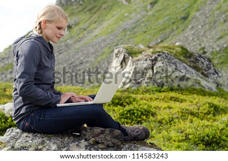 young blond woman sits with a laptop on a stone before mountain landscape - stock photo