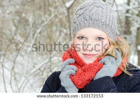 young blond woman smiles with grey beanie and orange scarf in the winter wood - stock photo