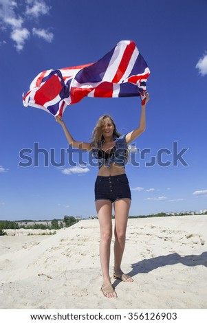 Young blond woman standing and waving British national flag in arms - stock photo