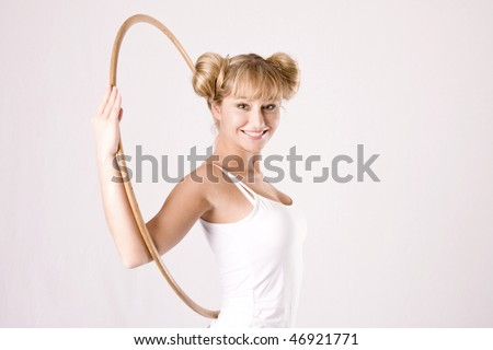 young blond woman takes athletic exercises with a hoop - stock photo