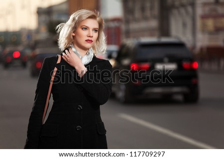 Young blond woman walking on the street - stock photo