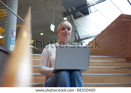 young blond woman with a laptop on the stairs/ woman with laptop - stock photo