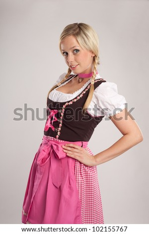 young blond woman with dirndl dress blows someone a kiss/young blond woman dressed with dirndl for oktoberfest/young blond woman with dirndl costume - stock photo
