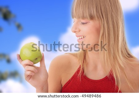 Young blond woman with green apple - healthy concept - stock photo
