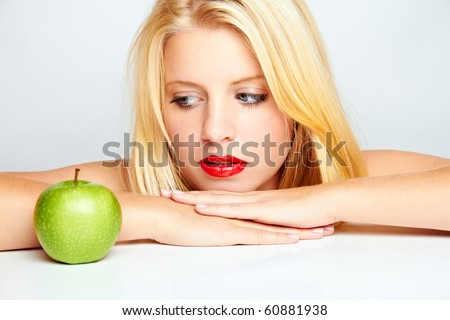 young blond woman with green apple on white ground - stock photo