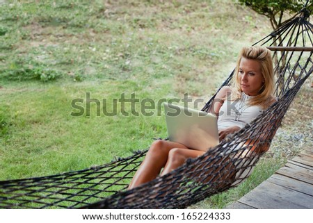 young blond woman with laptop in hammock - stock photo