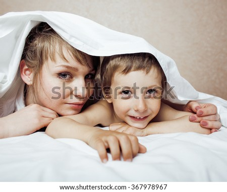 young blond woman with little boy in bed, mother and son, happy family - stock photo