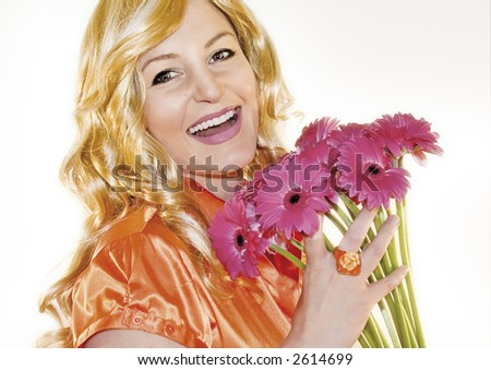 young blond woman with orange blouse holding pink flowers - stock photo