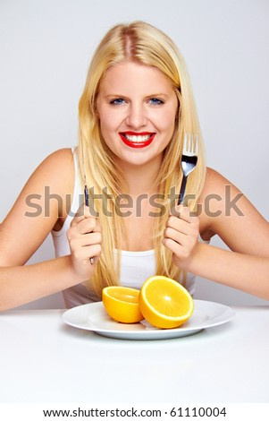 young blond woman with orange on a plate with silverware - stock photo