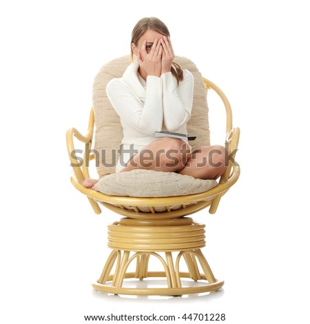 Young blond woman with remote control watching tv - scared - stock photo