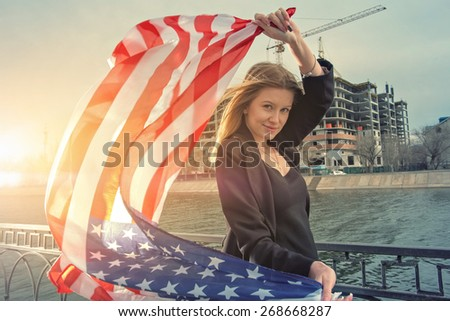 Young blond women posing with united states stars and stripes flag against pffice building construction backlit by sunset sun. - stock photo