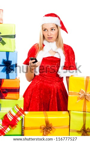 Young blond worried woman wearing Christmas Santa costume holding mobile phone, surrounded by gift boxes, isolated on white background. - stock photo