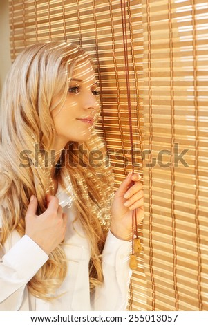 Young blonde beautiful happy woman looking out the window through the bamboo blinds with Sun hotspots on the face - stock photo