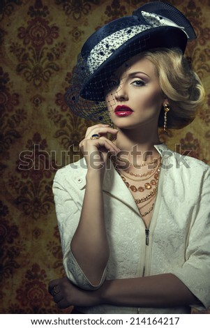 Young,blonde beautiful woman with old fashion style,  in expensive gold jewelry with smart blue hat with veil. - stock photo