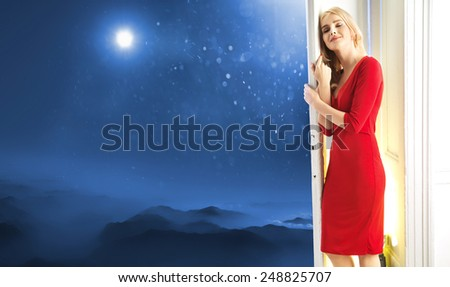 Young blonde beauty waiting at the door - stock photo