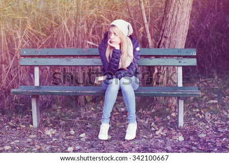 young blonde  bored girl on a bench - stock photo
