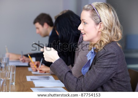 Young blonde businesswoman sitting at conference table and point something with her pen, - stock photo