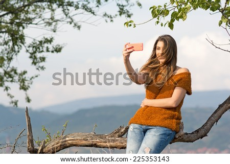 Young blonde Caucasian woman in park in autumn taking a selfie with smartphone. Beautiful teenage girl taking a self portrait outdoors in park on windy day. No retouch. - stock photo
