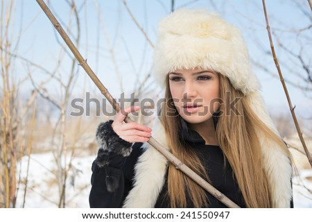 Young blonde Caucasian woman with white fur hat outdoors in winter. Closeup portrait of cute young teenage girl with long hair in park. No retouch or color filters. - stock photo