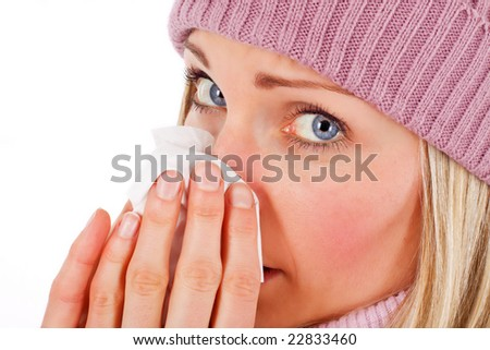 Young blonde female blowing her nose - isolated on white - stock photo