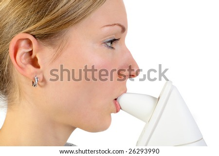 young blonde female using an inhalator to release her respiratory system - stock photo
