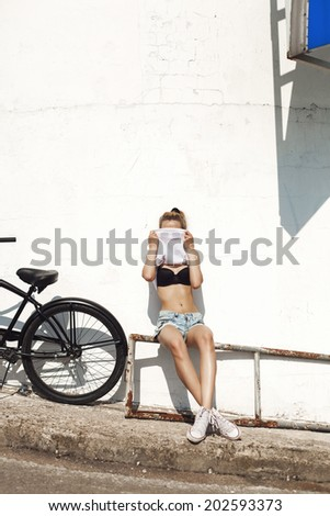 Young blonde girl covering her face T-shirt. Outdoors. Urban lifestyle shot. - stock photo