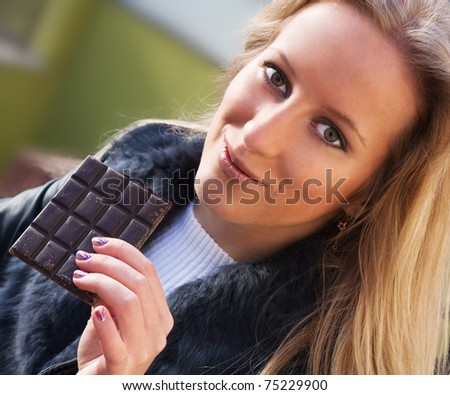 Young blonde girl eating a chocolate - stock photo