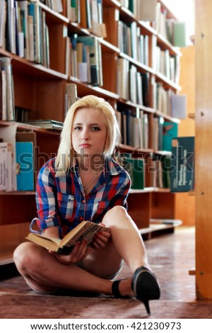 Young blonde girl in a plaid shirt with a book in hand sitting on the floor in the old library among the shelves - stock photo