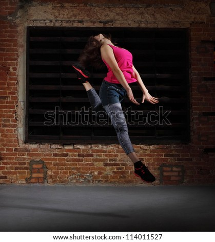 Young blonde girl jumping over brick wall - stock photo
