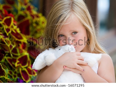 young blonde girl kissing bunny - stock photo