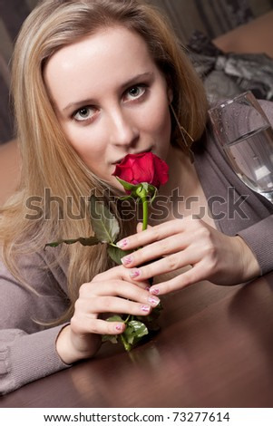 Young blonde girl with a red rose - stock photo