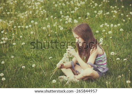 young blonde girl with bunch of dandelions on a green lawn - stock photo