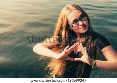 Young blonde making heart shape by her hands against water - stock photo
