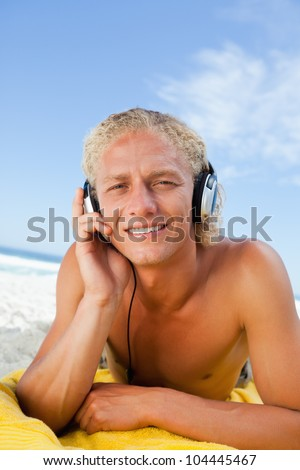 Young blonde man attentively listening to music while lying on then beach - stock photo