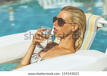 Young blonde model relaxing in pool drinking a glass of watter on a hot summers day - stock photo