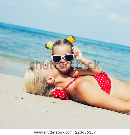 Young blonde mother and her little daughter having fun on the sea beach in summer. Outdoors - stock photo