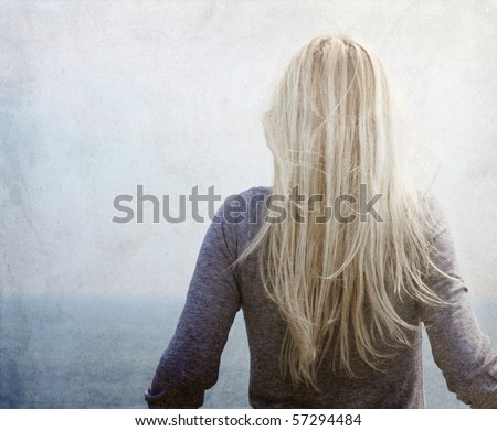 Young blonde near the sea. Photo in vintage colored image style. - stock photo