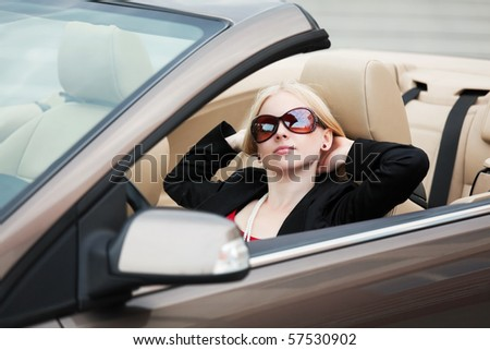 Young blonde relaxing in a convertible. - stock photo