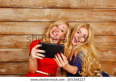 Young blonde sisters make fun group self, holding a tablet computer. Girls smiling. The concept of youth and technology. - stock photo