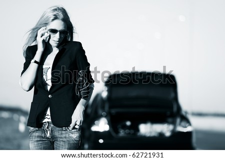 Young blonde with a broken car calling for help. - stock photo